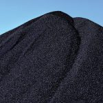 Tall pile of coal against blue sky