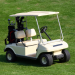 Golf cart with golf clubs in back on grass