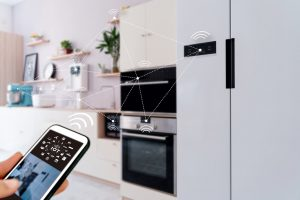 Smart home concept with hand holding cell phone controlling appliances in kitchen